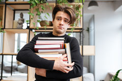 Confused caucasian student in library holding books. Photo of confused caucasian student in library learning education material and holding books in hands. Look Royalty Free Stock Photography