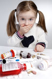Confused child. Confused little girl behind pile of medications Royalty Free Stock Photography