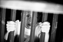 Confused child behind bars Royalty Free Stock Images