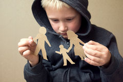 Confused child with broken paper family Stock Photos