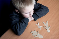 Confused child with broken paper family Royalty Free Stock Image