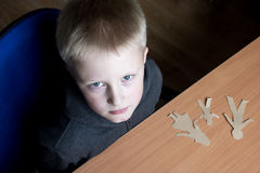 Confused child with broken paper family Stock Photo