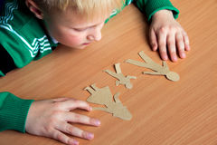 Confused child with paper family Stock Photography