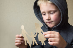 Confused child with paper family Royalty Free Stock Images