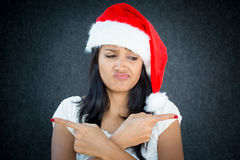 Confused. Closeup portrait of cute christmas woman with a red Santa Claus hat, white dress, fingers pointed in different directions, confused, which direction to Stock Image