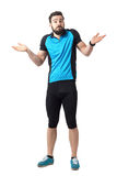 Confused clueless young athlete in cycling clothes shrugging shoulders. Full body length portrait isolated over white studio background Royalty Free Stock Images
