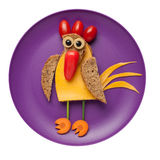 Confused cock made of bread, cheese and vegetables. On plate Royalty Free Stock Photos