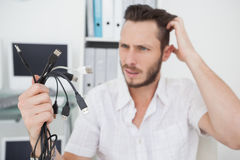 Confused computer engineer looking at wires Stock Image
