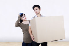 Confused couple bring box at new home Royalty Free Stock Photo