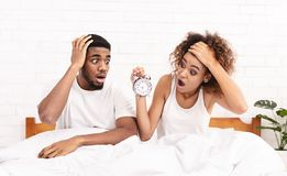 Confused couple missed ringing of alarm clock in bed. Oversleeping. Young african-american couple missed ringing of alarm clock and are late, sitting in bed stock images