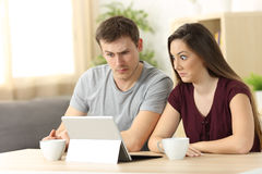 Confused couple receiving on line news Royalty Free Stock Photo