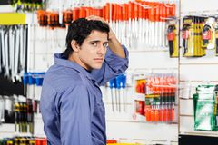 Confused Customer With Hand On Head In Hardware. Side view portrait of confused customer with hand on head in hardware shop Stock Photos