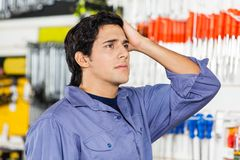 Confused Customer Looking Away In Hardware Shop Stock Photography