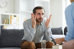 Man talking to counselor. Confused or desperate men sitting on couch and explaining what matters him during psychological session stock photo