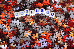 Confused. Dice spelling out the word confused sits on top of red and gray scattered puzzle pieces royalty free stock images