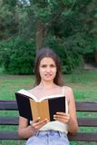 Confused and displeased girl is reading a book on the bench in the park stock photos