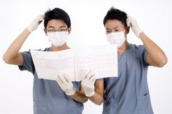 Confused Doctors. Two doctors are confused by a medical report Stock Photography