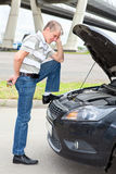 Confused driver standing front of car Stock Images