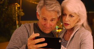 Confused elderly couple lost in a different country and uses smartphone for help Stock Photo