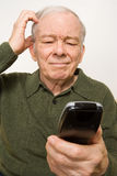 Confused elderly man with remote control Royalty Free Stock Photo