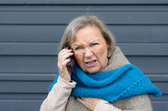Confused elderly woman chatting on her mobile Stock Photography