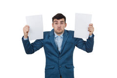 Confused emotion. Confused young businessman holding two white papers in hands, isolated on white background. Human emotion, face expression life perception Royalty Free Stock Image