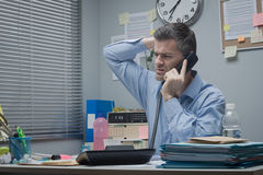Confused employee on the phone. At office desk touching his head Royalty Free Stock Photos