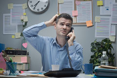 Confused employee on the phone. At office desk touching his head Stock Photography