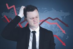 Confused entrepreneur with declining finance graph. Young Caucasian entrepreneur looks confused and scratching head with declining finance graph background Royalty Free Stock Images