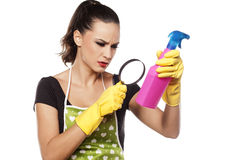 Confused fashionable housewife. Confused young housewife reading the label on the spray bottle through magnifyer Royalty Free Stock Images