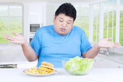 Confused fat person choosing salad or hamburger. Photo of a fat person looks confused to choose a bowl of salad or hamburger on the plate, shot in the kitchen royalty free stock photos