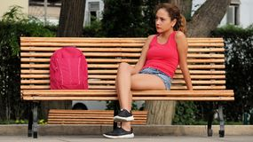 Confused Female College Student On Park Bench Stock Photo