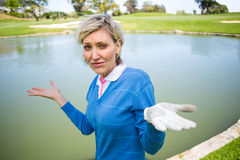 Confused female golfer looking at lake Royalty Free Stock Photos