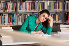 Confused Female Student Reading Many Books For Exam Stock Photo