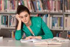 Confused Female Student Reading Many Books For Exam Stock Photography