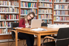 Confused Female Student Reading Many Books For Exam Stock Images