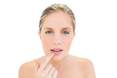 Confused fresh blonde woman touching her lip Stock Images