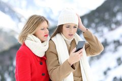 Confused friends with a smart phone in winter Stock Photo