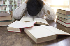 Confused and frustrated man with textbook stack on wooden desk. Confused and upset man with textbook stack on wooden desk in library Stock Photo