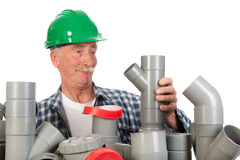 Confused funny plumber. Plumber confused by assortment pvc tubes Royalty Free Stock Images