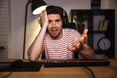 Confused gamer playing video games on computer. While sitting by the table at home royalty free stock photo