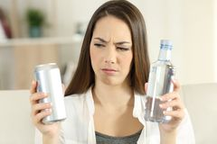 Confused girl deciding between soda refreshment and water. Front view portrait of a confused girl deciding between soda refreshment and water bottle at home Stock Image