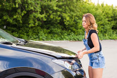 Confused girl did not know what to do with a car that broke down on the road.  Royalty Free Stock Images