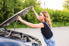 Confused girl did not know what to do with a car that broke down on the road.  Royalty Free Stock Photo