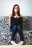 Confused girl with laptop. Sitting on the sofa and looking at camera Royalty Free Stock Photo