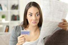 Confused girl reading leaflet of contraceptive pills Royalty Free Stock Photos