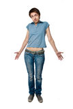 The confused girl shrugs shoulders. The confused girl in jeans and a T-shirt shrugs shoulders Stock Photography