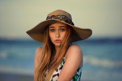 Confused girl thinking on the ocean beach. Beautiful young girl wearing hat and having fun Royalty Free Stock Image