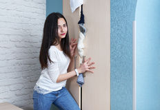 Confused girl trying to close  full wardrobe Royalty Free Stock Photo
