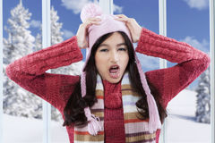 Confused girl with winter clothes at home. Portrait of confused girl wearing sweater and screaming at home while holding her head Royalty Free Stock Photography